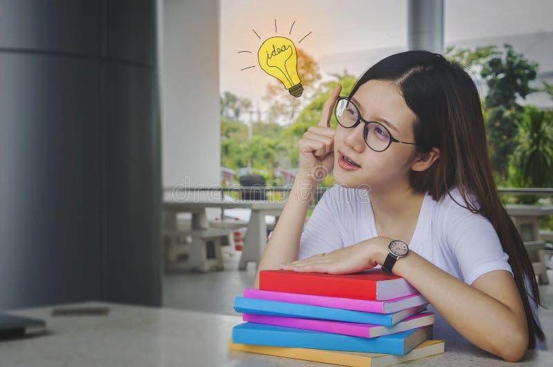 Menina de pensamento do estudante da ideia com vidros e livros na mesa, furada imagem de stock