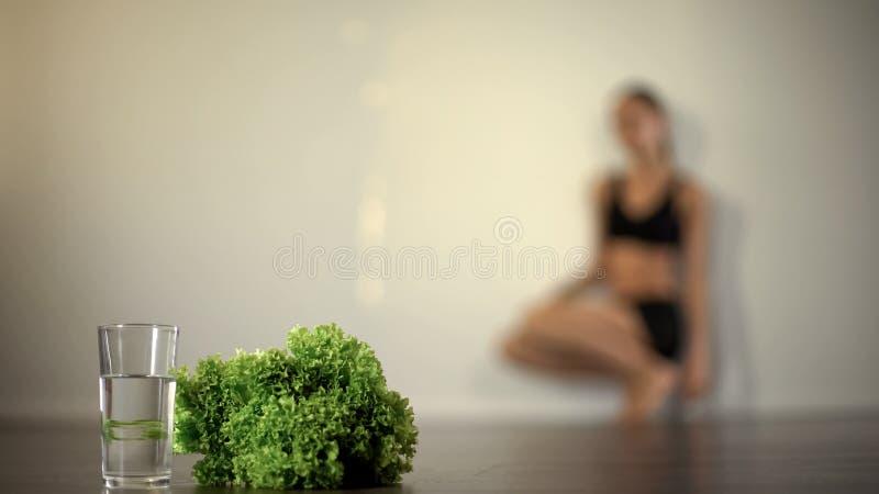 A menina de pouco peso desmaia devido à dieta severa, alimento jejuando, distúrbio alimentar imagem de stock