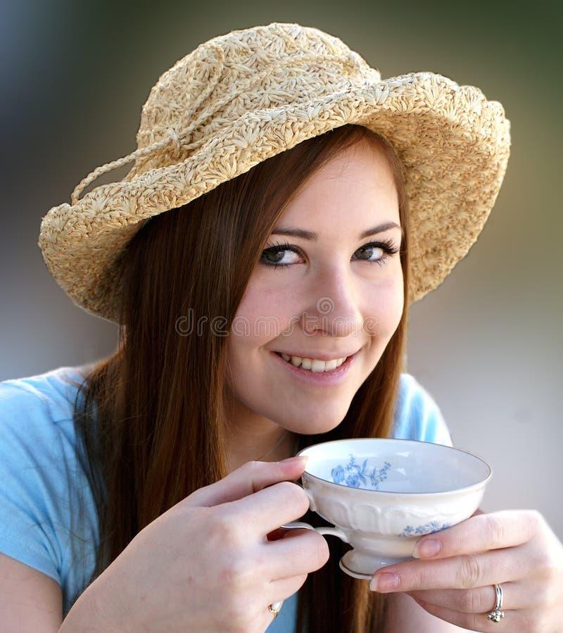 A menina de Preetty sorve o chá do copo de chá inglês ilustração royalty free