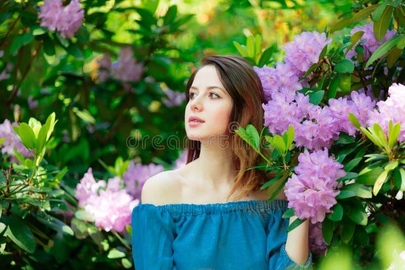Menina de Redehad em flores do arbusto da flor imagens de stock royalty free