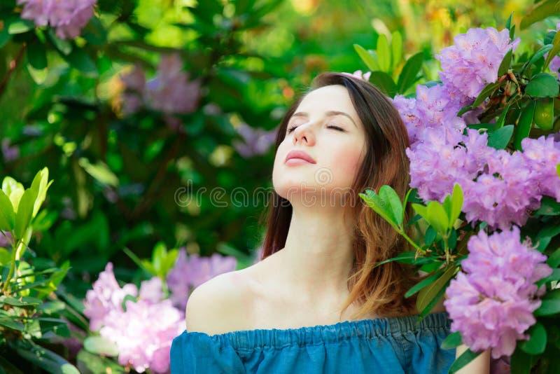 Menina de Redehad em flores do arbusto da flor imagens de stock
