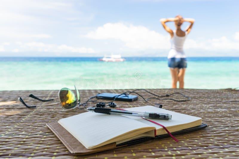 A menina de relaxamento, bloco de notas vazio aberto está na tabela com óculos de sol, telefone e fones de ouvido no fundo tropic fotografia de stock royalty free