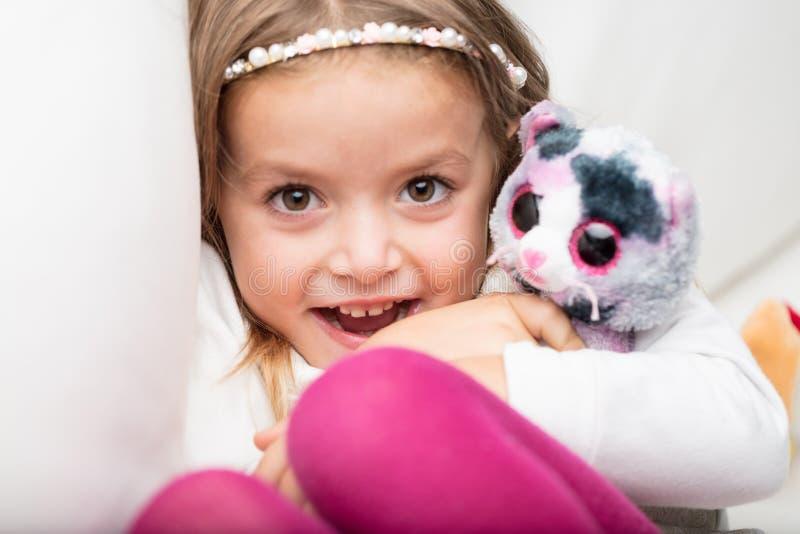 Menina de riso bonito com seu brinquedo macio imagens de stock