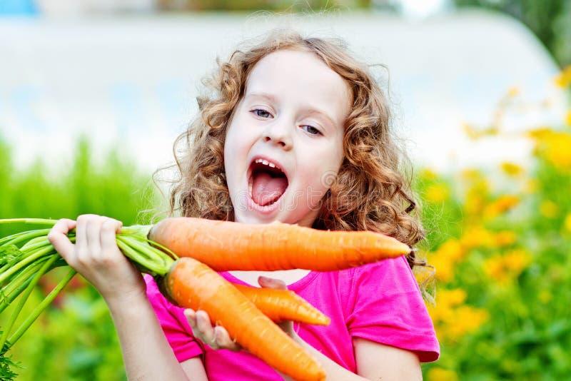 Menina de riso com a cenoura amarela no jardim foto de stock