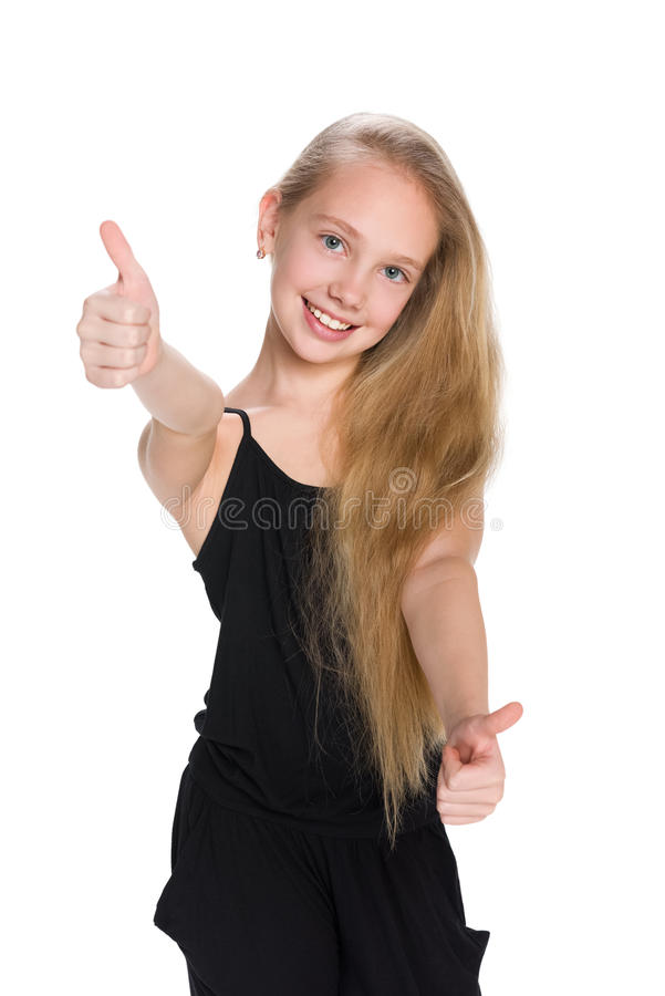 A menina de riso do preteen mantém seus polegares imagens de stock royalty free