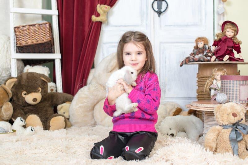 Menina de riso feliz que joga com um coelho do bebê, abraçando seu animal de estimação real do coelho e aprendendo tomar de um an imagem de stock