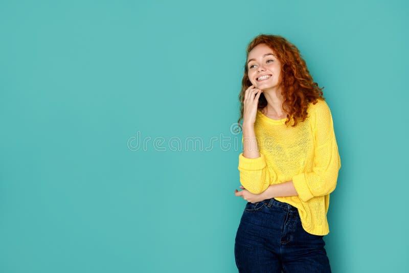 Menina de riso na roupa ocasional que levanta no estúdio foto de stock
