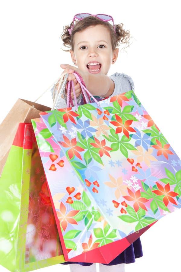 Menina de riso pequena com os sacos de compra sobre o branco fotografia de stock