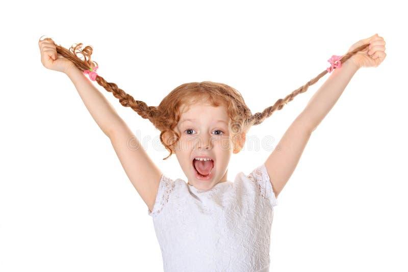 A menina de riso puxa para cima suas tranças à mão e mostra-a que sai os dentes foto de stock royalty free