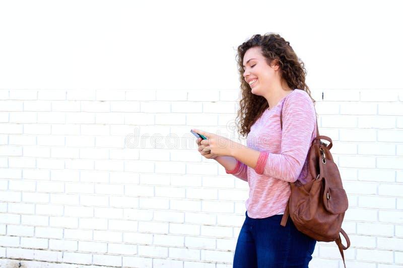Menina de riso que está e que texting com trouxa imagem de stock