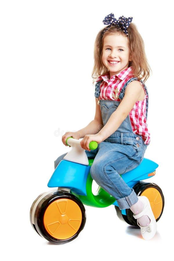 Menina de riso que monta uma bicicleta pequena fotografia de stock