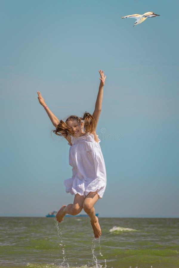 Menina de riso que salta sobre o mar imagem de stock