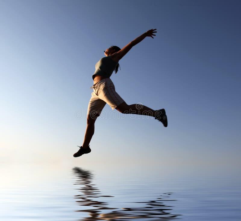 Menina de salto fantástica sobre a água fotografia de stock