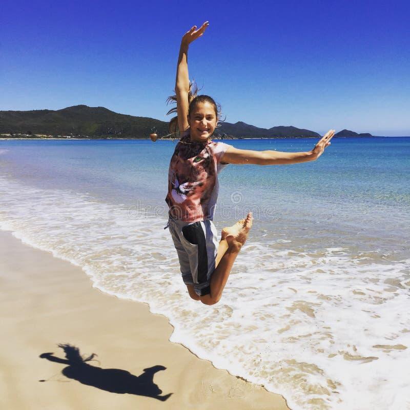 Menina de salto na praia imagem de stock