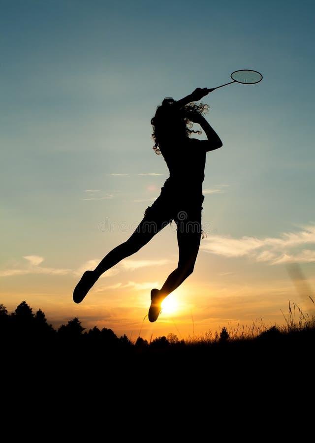 Menina de salto que joga o badminton imagem de stock