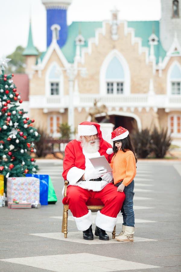 Menina de Santa Claus Showing Digital Tablet To foto de stock