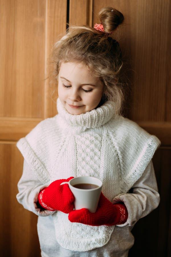 A menina de sete anos de encantamento bebe o chá morno, estando ao lado da janela Está vestindo uma camiseta feita malha morna, e fotos de stock