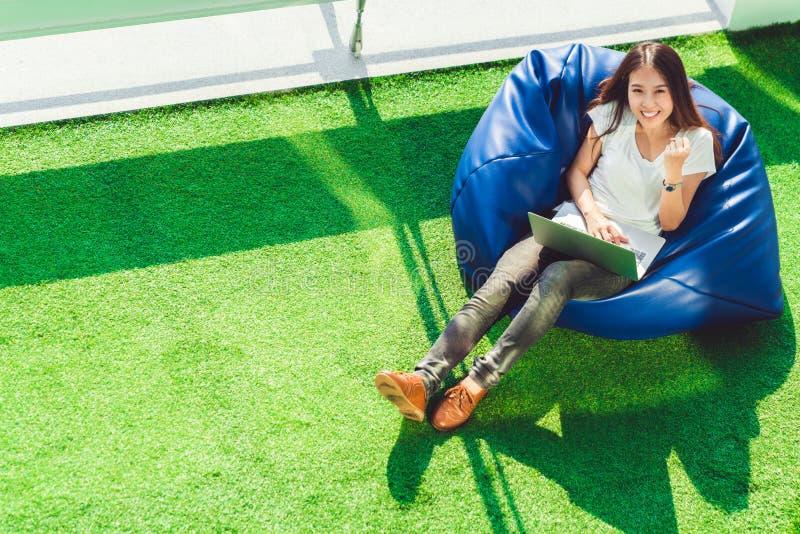 A menina de Sião comemora com portátil do caderno, senta-se no saco de feijão no jardim Empresa de pequeno porte do sucesso, conc fotografia de stock