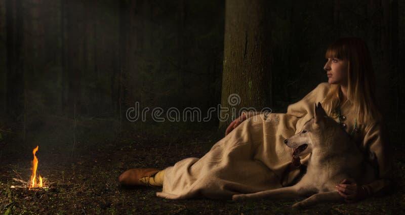 Menina de Slavonian e cão de puxar trenós siberian na floresta profunda foto de stock