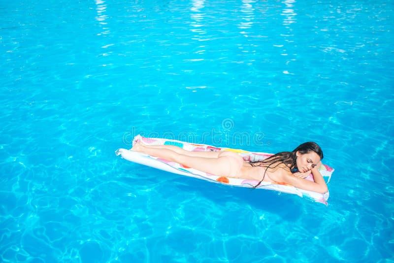 A menina de Sleppy está encontrando-se no colchão iar e na refrigeração Obtém algum bronzeado A jovem mulher é no meio da piscina imagens de stock