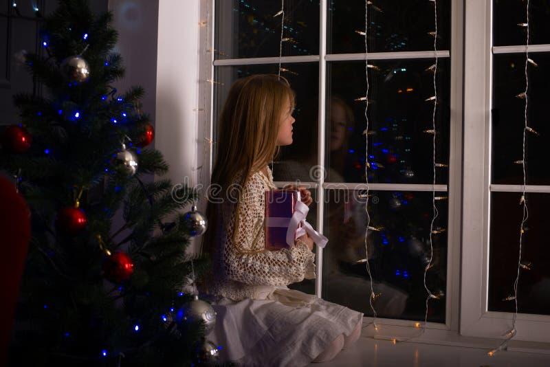 Menina de sonho em antecipação a um milagre em um Natal fotos de stock
