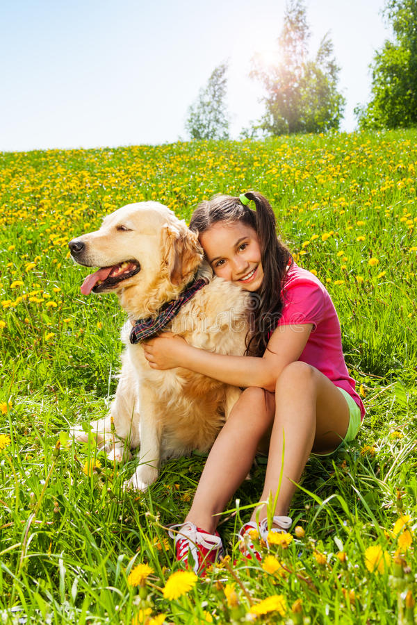 A menina de sorriso abraça o cão bonito que senta-se na grama fotografia de stock royalty free