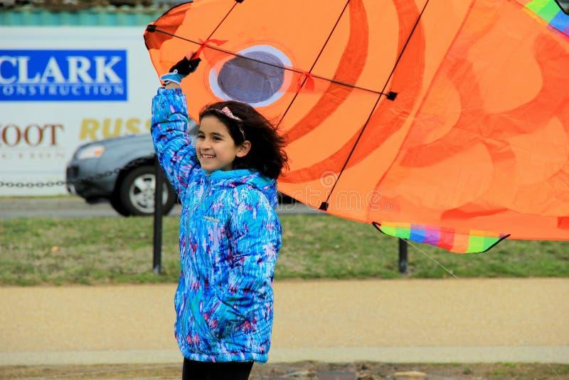 A menina de sorriso adorável, apronta-se para voar seu papagaio, festival do papagaio, Washington, C.C., 2015 foto de stock