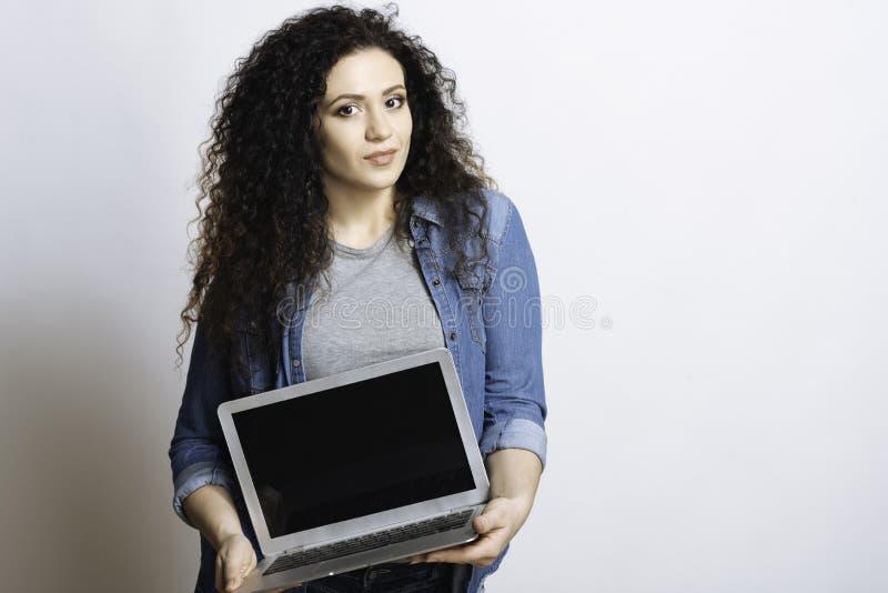 Menina de sorriso agradável que guarda um computador imagem de stock