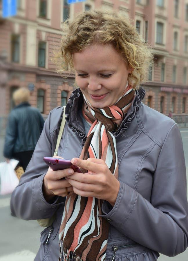 Menina de sorriso agradável que lê uma mensagem de telefone fotos de stock