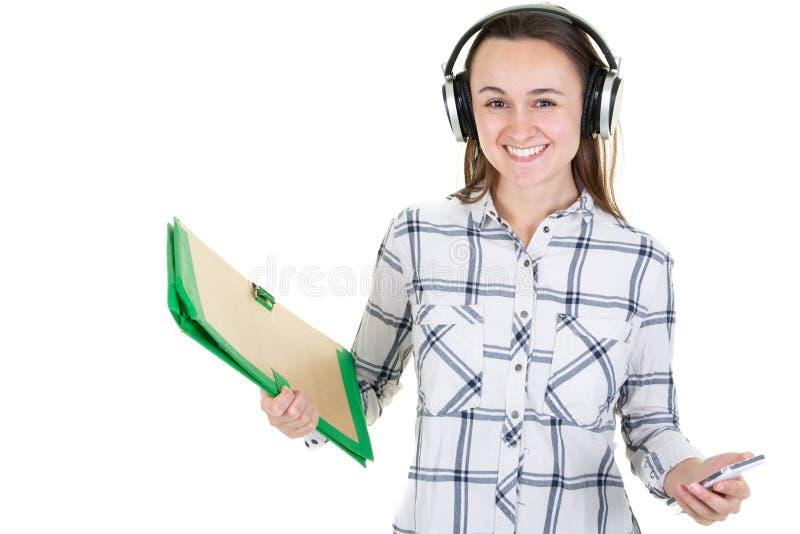 Menina de sorriso alegre do estudante com os fones de ouvido da música que mantêm livros isolados sobre o fundo branco imagem de stock royalty free