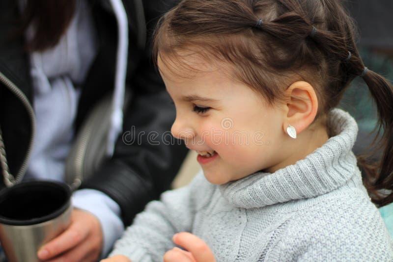 menina de sorriso alegre pequena bonita com sua mãe em uma caminhada na rua fotografia de stock royalty free