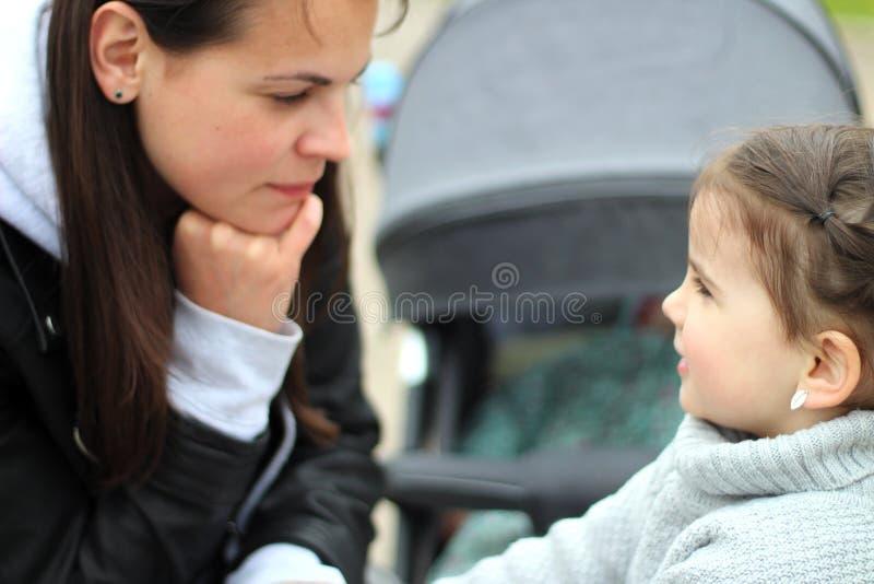 menina de sorriso alegre pequena bonita com sua mãe em uma caminhada na rua fotos de stock royalty free