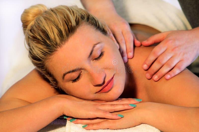 A menina de sorriso aprecia na tabela da massagem imagem de stock
