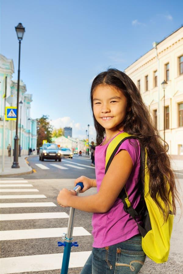 Menina de sorriso asiática no 'trotinette' perto da estrada transversaa imagem de stock