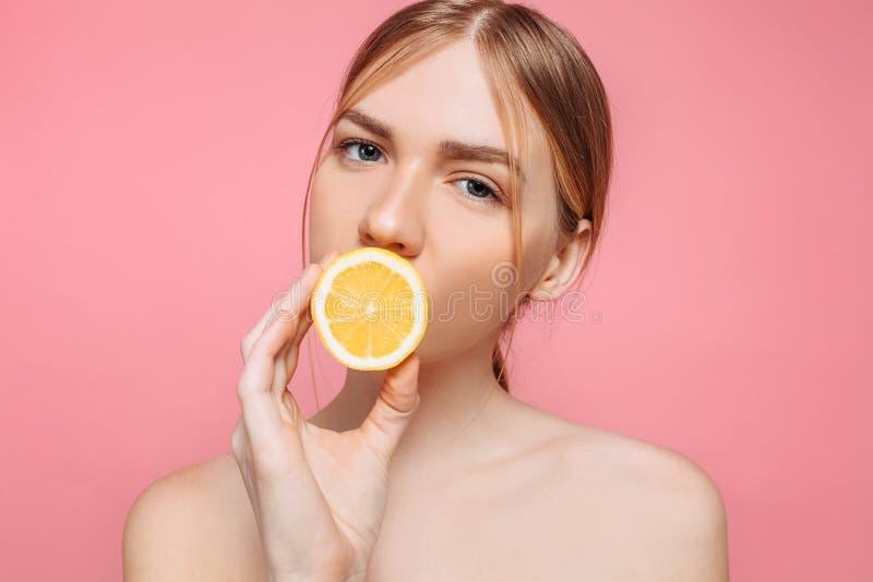 Menina de sorriso atrativa com pele limpa e limão em um fundo cor-de-rosa foto de stock