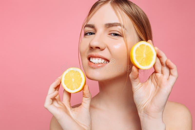 Menina de sorriso atrativa com pele limpa e limão em um fundo cor-de-rosa fotos de stock royalty free
