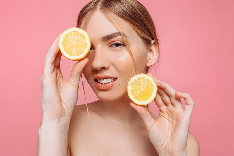 Menina de sorriso atrativa com pele limpa e limão em um fundo cor-de-rosa fotos de stock