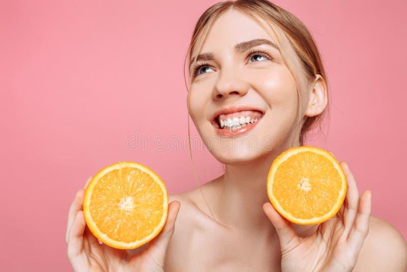 Menina de sorriso atrativa com pele limpa e partes alaranjadas em um fundo cor-de-rosa fotografia de stock royalty free