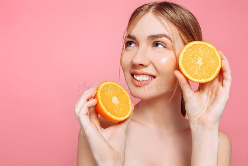Menina de sorriso atrativa com pele limpa e partes alaranjadas em um fundo cor-de-rosa fotografia de stock