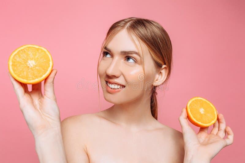 Menina de sorriso atrativa com pele limpa e partes alaranjadas em um fundo cor-de-rosa foto de stock royalty free