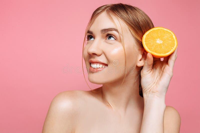 Menina de sorriso atrativa com pele limpa e partes alaranjadas em um fundo cor-de-rosa imagens de stock royalty free