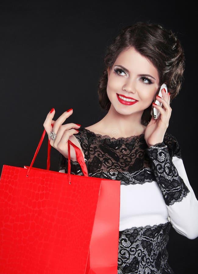 Menina de sorriso atrativa com sacos de compras vendas Woma de riso imagens de stock royalty free