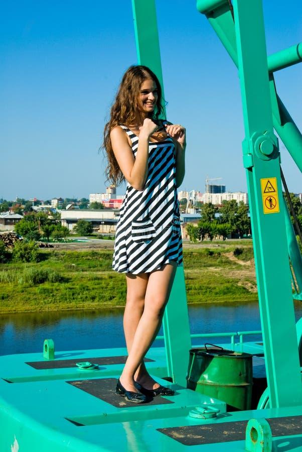 Menina de sorriso atrativa no guindaste de construção fotografia de stock royalty free