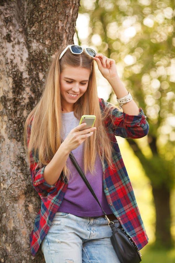 Menina de sorriso atrativa que texting no telefone celular, exterior Mulher feliz moderna com um smartphone imagens de stock royalty free