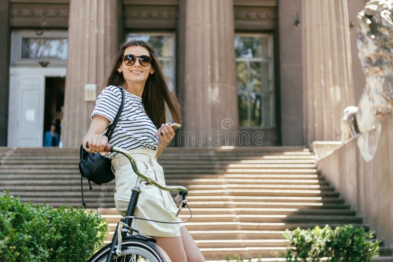 menina de sorriso atrativa que usa o smartphone ao sentar-se na bicicleta perto da construção bonita com colunas foto de stock royalty free