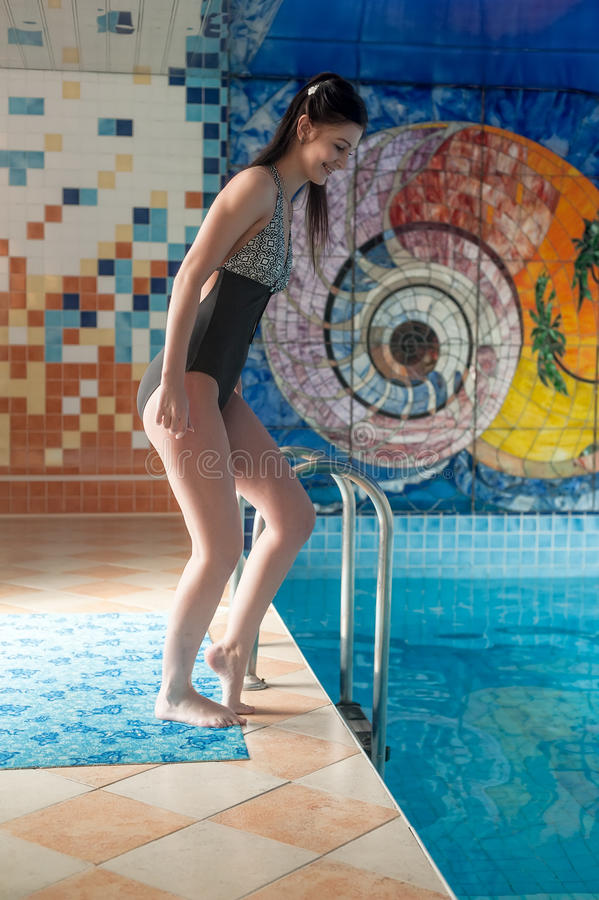 A menina de sorriso atrativa relaxa na piscina fotografia de stock royalty free