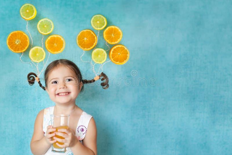 A menina de sorriso bebe o suco de laranja fresco fotos de stock