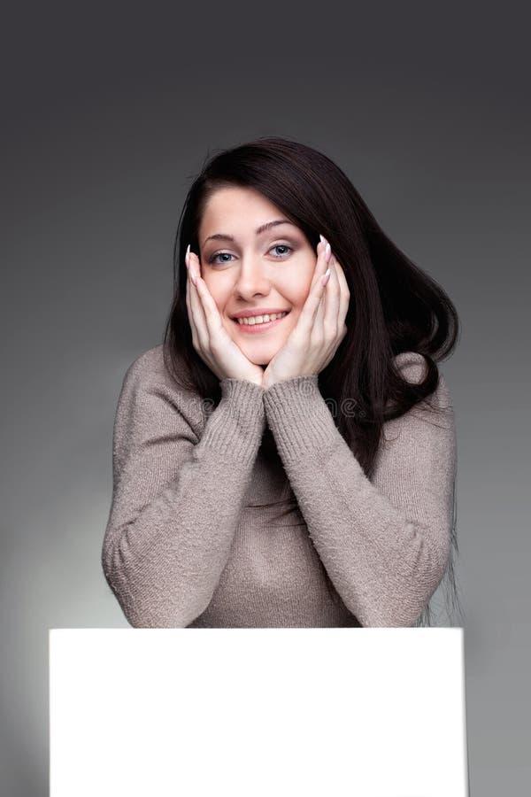 Menina de sorriso bonita atrás da placa vazia fotos de stock