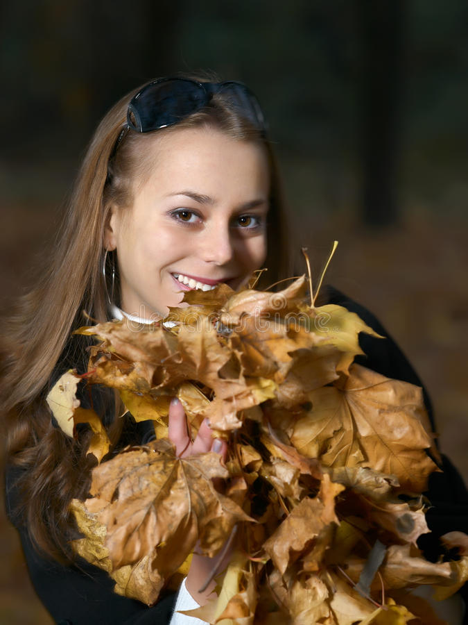 Menina de sorriso bonita com armful das folhas foto de stock