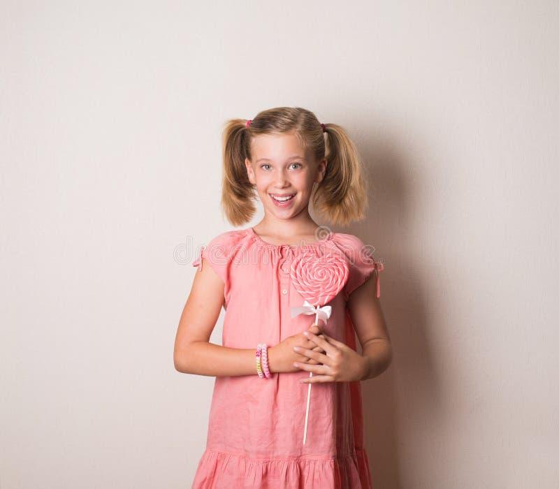 A menina de sorriso bonita com coração grande deu forma ao pirulito imagens de stock royalty free